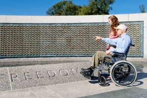 A man and his granddaughter at a memorial celebrating veterans. Contact a Greenville Veterans Disability Attorney