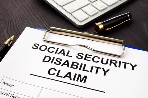 A social security disability form next to a keyboard.